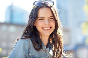 cosmetic dentistry woodlands tx, brunette woman with sunglasses smiling