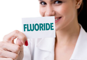 fluoride treatments tx, woman holding a piece of paper reading fluoride